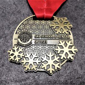 medaglia personalizzata scuola sci ortisei in metallo a rilievo 2D finitura bronzoe antico con nastro rosso