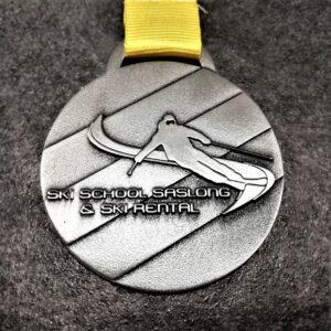 medaglia personalizzata scuola sci saslong in metallo a rilievo 2D finitura argento antico con nastro personalizzato in serigrafia
