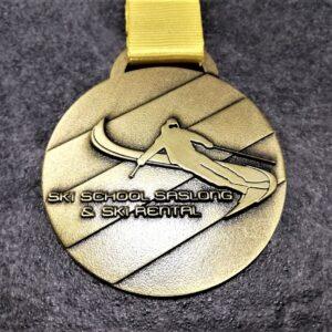 medaglia personalizzata scuola sci saslong in metallo a rilievo 2D finitura bronzo antico con nastro personalizzato in serigrafia