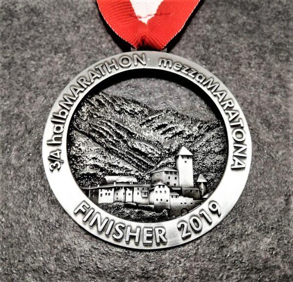 medaglia personalizzata 3 quarti mezza maratona brunico 2019 traforata in metallo a rilievo 3D finitura argento antico con nastro biancorosso