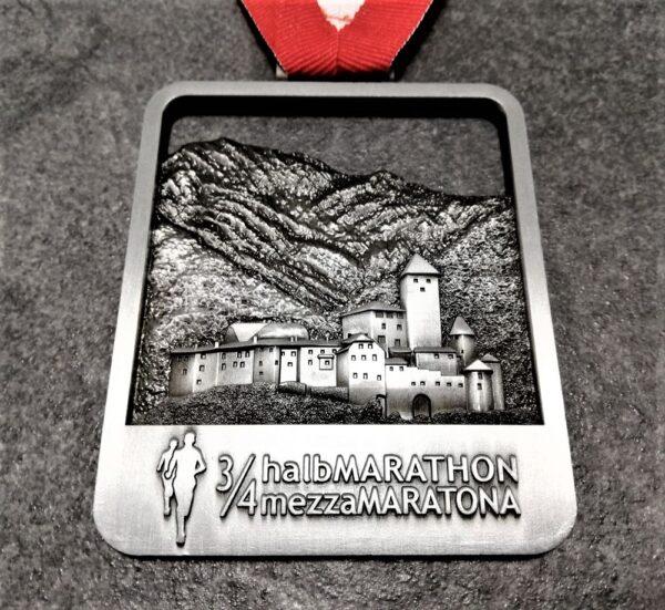 medaglia personalizzata 3 quarti mezza maratona brunico traforata in metallo a rilievo 3D finitura argento antico con nastro biancorosso