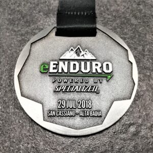 medaglia personalizzata enduro san cassiano in metallo a rilievo 2D con smalti finitura argento antico con nastro personalizzato in sublimazione