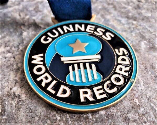 medaglia personalizzata guinness world records in metallo a rilievo 2D con smalti finitura oro satinato con nastro blu