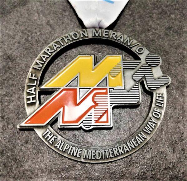 medaglia personalizzata half marathon merano 2019 in metallo a rilievo 2D traforata con smalti finitura argento antico con nastro personalizzato in sublimazione