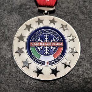 medaglia personalizzata scuola sci alpe di siusi in metallo a rilievo 2D con smalti finitura argento lucido satinato con nastro personalizzato in serigrafia