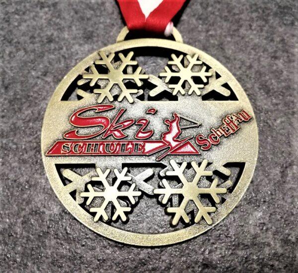 medaglia personalizzata ski schule scheffau in metallo a rilievo 2D con smalto traforata finitura bronzo antico con nastro rossobiancorosso