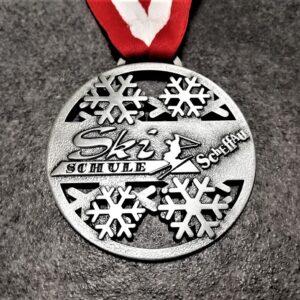 medaglia personalizzata ski schule scheffau in metallo a rilievo 2D traforata finitura argento antico con nastro rossobiancorosso