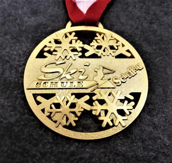 medaglia personalizzata ski schule scheffau in metallo a rilievo 2D traforata finitura oro satinato con nastro rossobiancorosso