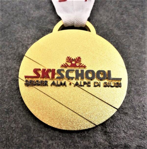 medaglia personalizzata skischool seiser alm alpe di siusi in metallo a rilievo 2D con serigrafia finitura oro lucido satinato con nastro personalizzato in serigrafia