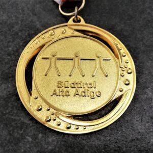 medaglia personalizzata sport scolastico sudtirol alto adige in metallo a rilievo 2D traforata finitura oro lucido e satinato con nastro biancorosso
