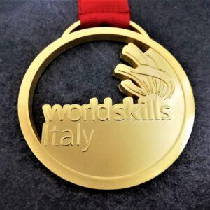 medaglia personalizzata world skills italy in metallo a rilievo 2D traforata finitura oro satinato con nastro personalizzato in serigrafia